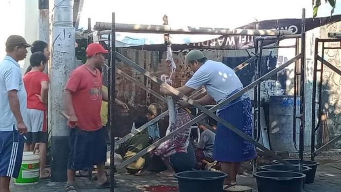 Umat non muslim membantu umat muslim saat penyembelihan hewan kurban di Masjid.