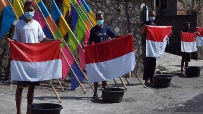 Sejumlah warga melakukan tradisi unik mencuci bendera Merah Outih secara bersama untuk menyambut HUT ke-76 Kemerdekaan RI di Dukuh Beji, Desa Sidomulyo Ampel, Kabupaten Boyolali, Jawa Tengah, Minggu, 8 Agustus 2021.
