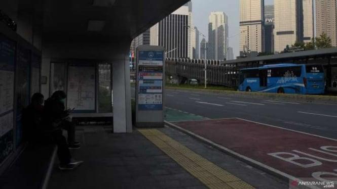 Calon penumpang menunggu bus TransJakarta di Halte Bundaran Senayan 2, Jakarta.