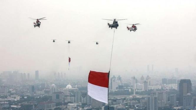 Helikopter TNI AU membawa bendera raksasa saat HUT RI ke 76 di atas Istana