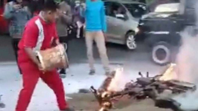 Seorang petugas SPBU terlihat menyiram motor yang terbakar dengan air.