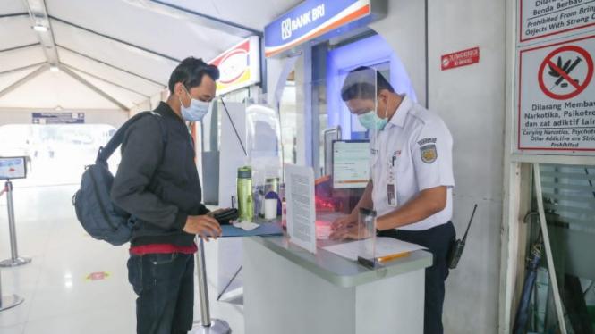 Petugas KAI mengecek dokumen penumpang.