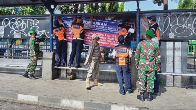Petugas gabungan memasang spanduk di Halte KPPN Jalan H Juanda Kota Bogor.