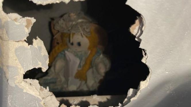 Seorang penghuni rumah baru di Inggris menemukan boneka di dalam dinding.