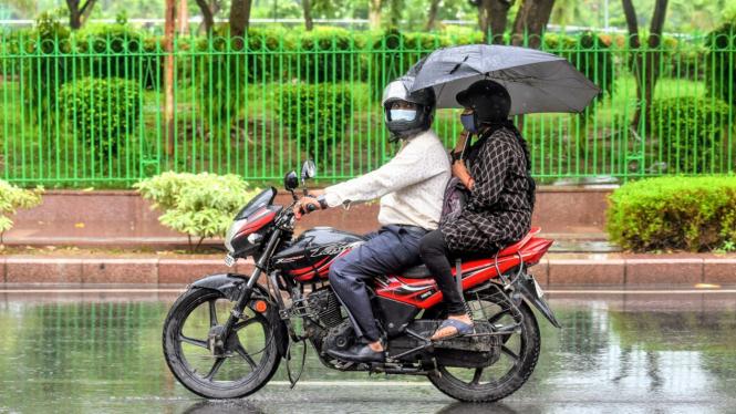 Ilustrasi naik motor sambil membawa payung.