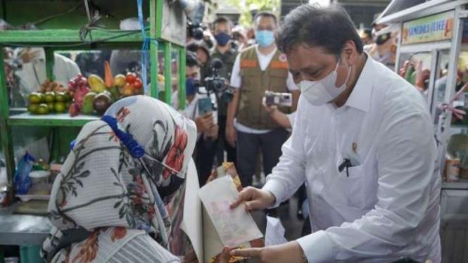 Menko Perekonomian Airlangga Hartarto memberikan bantuan kepada seorang PKL.