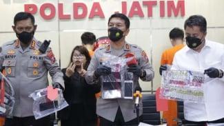 Tiga orang tersangka dan barang bukti penagih pinjol ilegal diperlihatkan oleh polisi di Markas Polda Jawa Timur di Surabaya, Senin, 25 Oktober 2021.